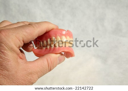 a human hand holds Genuine Dentures AKA False Teeth from a Dentist Office on grey - stock photo