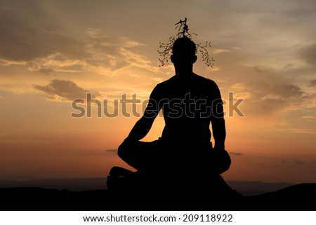 A human silhouette meditating at sunset.