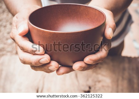 a hungry man holding an empty bowl - stock photo
