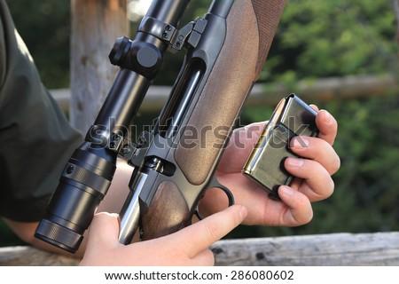 A Hunter loading his hunting rifle gun with magazine - stock photo