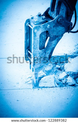 a hydraulic arm with impact breaker at work,broken concrete pavement - stock photo