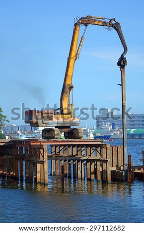A hydraulic pile driver sinks a large support post into the river bed for bridge construction. The letters in the back say port.  - stock photo