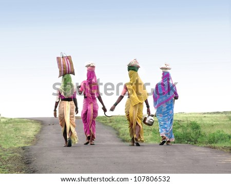 A image showing 4 Indian village women returning to home after completing there work with the tools & bag in traditional clothes. - stock photo