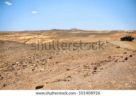 A j4x4 car on a desert path reaches the point of view on a desert panorama