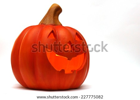 A Jack O Lantern made from clay depicting a smiling face with glowing inner cavity - stock photo