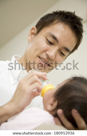 A Japanese father helping his child drink milk
