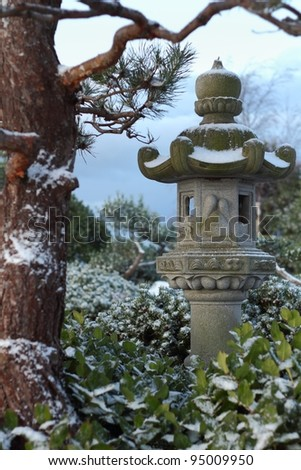 A Japanese stone lantern covered in a dusting of fresh snow in a Japanese garden.