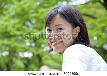 A  Japanese student smiling surrounded by nature,