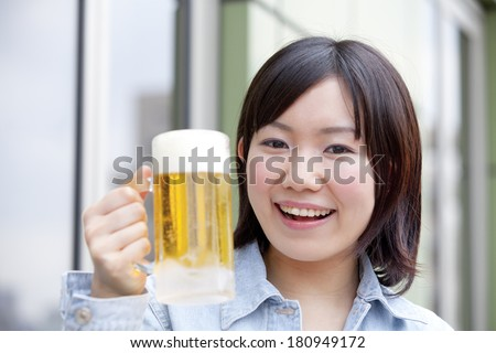A Japanese student smiling while holding a mug,