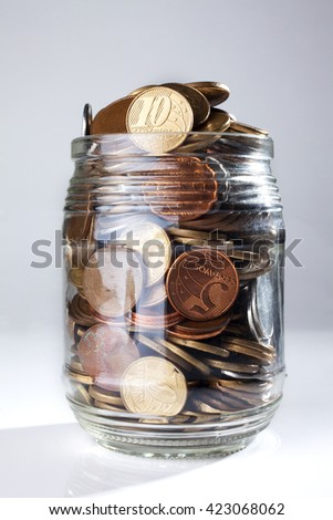 A jar full of Brazilian coins isolated on white background - stock photo