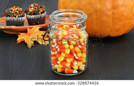 A jar of candy corn in a rustic mason jar.  Autumn background with a pumpkin, leaves and fall cupcakes.