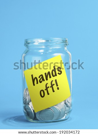 A jar of coins, with hands off note inside the jar.  - stock photo
