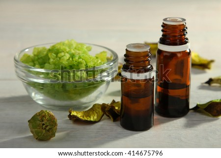 a jars with essential oilsl near the bowl with bath salt and the dry leaves on white wooden background - stock photo