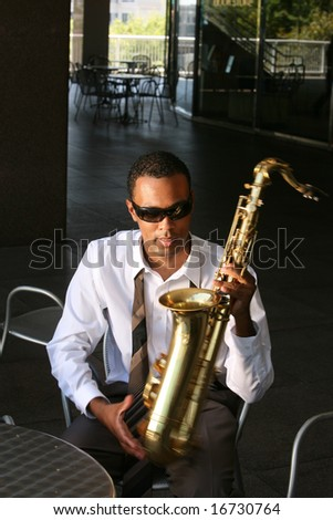 a jazz musician plays his saxophone - stock photo