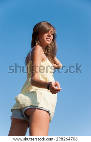 A jean short and yellow shirt for a young slim lady. A deep blue sky as background. She is standing almost with her back - stock photo