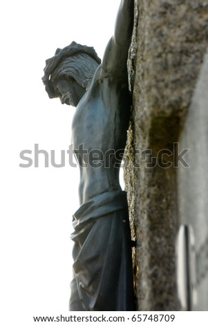 A Jesus figure at the cross. The cross is made of stone - stock photo