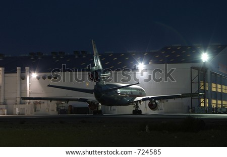 A jet airplane parked near its maintenance hangar. All visible airline markings have been removed. - stock photo