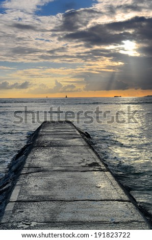 A jetty and  god rays over the ocean during sunset at Waikiki Beach, Hawaii. - stock photo