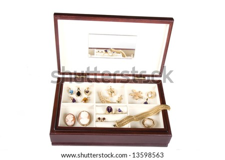 A jewelry box draped with jewels and gold