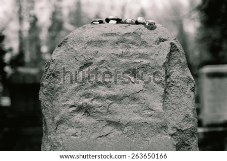 A Jewish headstone in cemetery with stones placed on it by visitors, in accordance with Jewish custom - stock photo