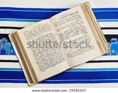 A Jewish prayer book, or Siddur, open and on top of a Jewish prayer shawl or Tallit.