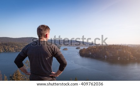 A jogger looking out from the top of a mountain onto the ocean. - stock photo