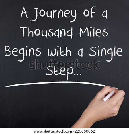 A Journey of a Thousand Miles Begins with a Single Step / Inspirational Motivational Quote Handwriting on Chalkboard - stock photo