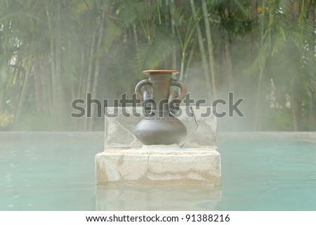 A jug in the middle of hot spring bath with thin steam. - stock photo