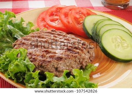 A juicy grilled ground beef patty with cucumbers nad lettuce - stock photo
