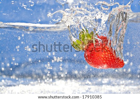 A juicy red strawberry plunging into some water. Shallow depth of field. - stock photo
