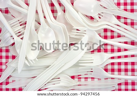 A jumble of white plastic forks, knives and spoons on a vinyl checkerboard tablecloth. - stock photo