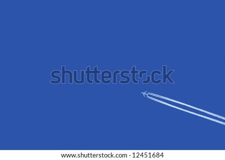 a jumbo jet flies across a blue sky leaving vapour trails - stock photo