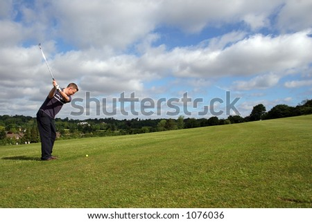 A junior golf champion prepares to lift the ball to the green - stock photo