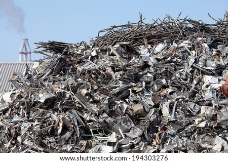 A junk pile of metal in front of a building. - stock photo