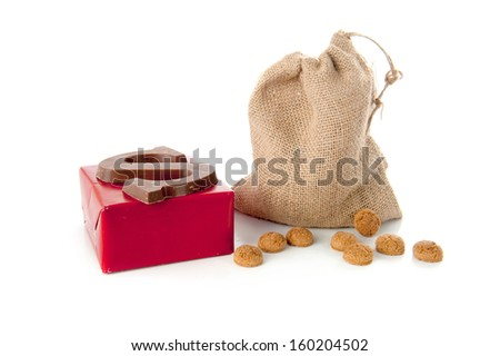 "A jute bag full of pepernoten, a present and a chocolate letter, for celebrating a dutch holiday "" Sinterklaas ""  on the fifth of December - stock photo"