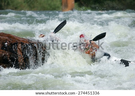 A K2 canoe with two paddlers crashes into a rock on a wild rapid in a river. - stock photo