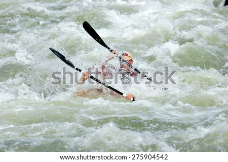 A K2 canoe with two paddlers is completely submerged as it navigates a wild rapid in a river. - stock photo