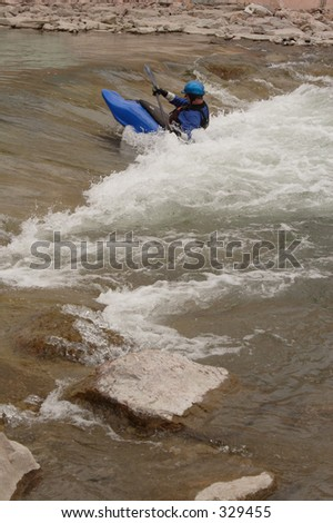 A kayaker plays in the atificial rapids created in the Arkansas River near downtown Pueblo, Co, taken in May, 2005. - stock photo