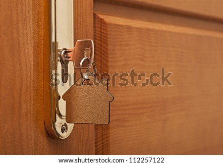 A key in a lock with house icon on it - stock photo