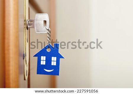 A key in a lock with house icon with smile on it  - stock photo