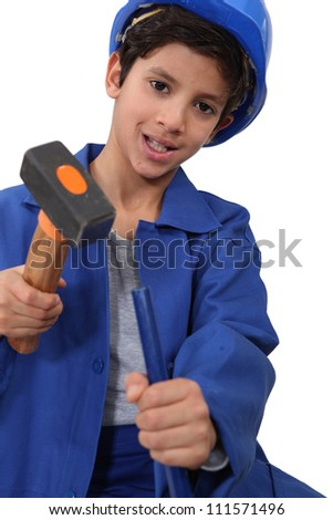 A kid dressed as a construction worker with a hammer. - stock photo