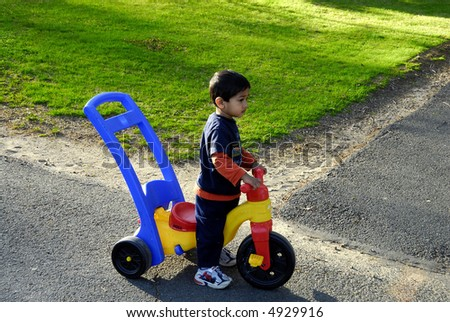 A kid having fun with a tricycle - stock photo