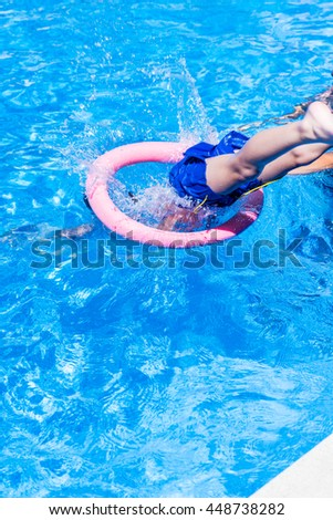 A kid jumps to dive in a swimming pool through a doughnut during a game.