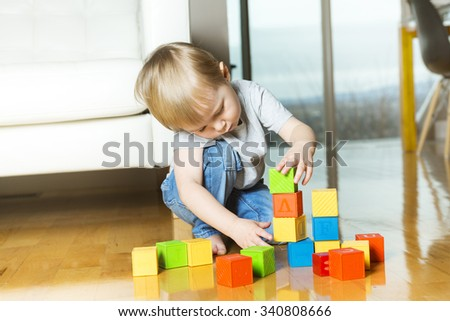 A kid playing toy blocks inside his house - stock photo