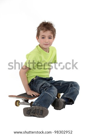 A kid sitting on his skateboard. - stock photo