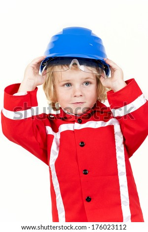A kid standing and holding a safety hat on his head. - stock photo