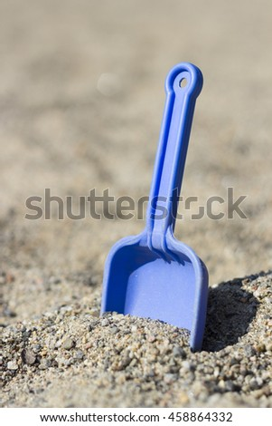 A kids spade is put in the sand