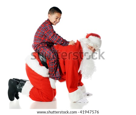 """A kindergarten boy happily playing """"horsie"""" with Santa Claus.  Isolated on white. - stock photo"""