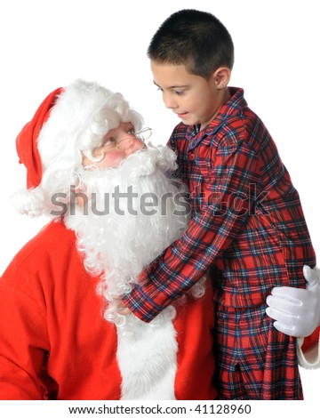 A kindergarten boy in plaid pajamas hugging Santa as he hugs back.  Isolated on white. - stock photo