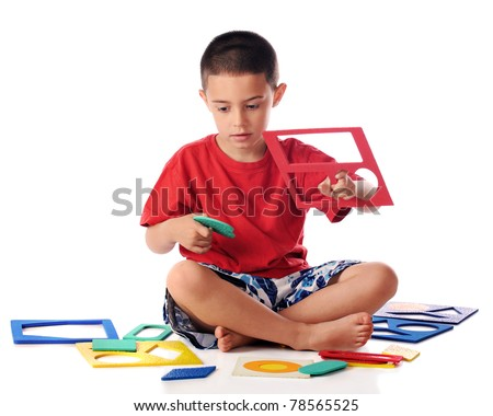 A kindergartner putting together a puzzle of colorful shapes.  Isolated on white. - stock photo
